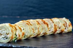 Vorspeise aus in Rollen geschnittener Omelette lecker gefüllt mit Hüttenkäse und Kräutern in Reihe