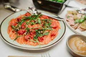 Vorspeise mit Lachs, Paprika, Kapern und Rucola auf einem Teller Nahaufnahme