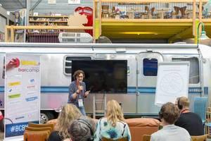 Vortrag für Digitalinteressierte zum Thema Digitale Kommunikation, während des Barcamps Bonn, vor einem alten amerikanischen Wohnmobil