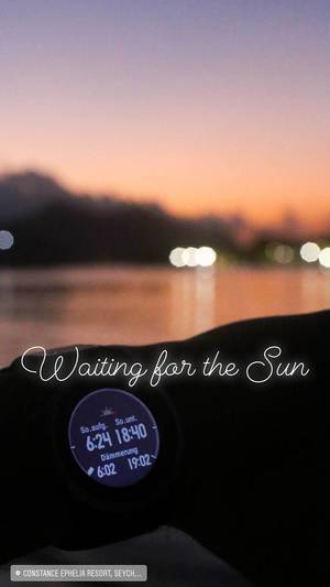 Waiting for the sunrise with Smart Watch showing sunrise hour and the Indian Ocean in the background in Mahé, Seychelles