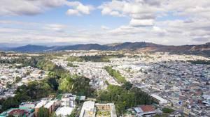 Wald in mitten der Großstadt Guatemala City mit Bergen im Hintergrund