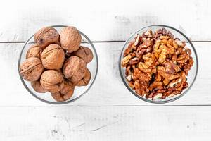 Walnut kernels and whole nuts in glass bowls