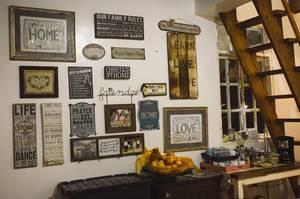 Wanddekoration aus Bildern, Tafeln und Zitaten im Vintage-Stil in Ferienwohnung