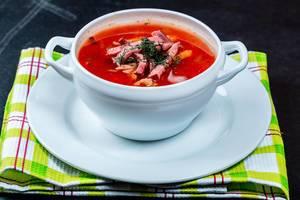 Warme Soljanka Suppe in einer Terrine, auf einem grünen Küchentuch