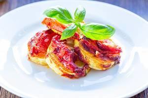 Warmes Mittagessen mit gebackenen Zucchini, Tomaten und Basilikumblätter, auf einem weißen Teller