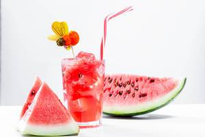 Watermelon drink in glass with slices of watermelon