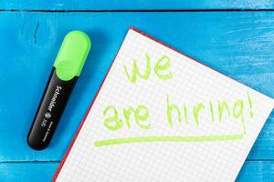 We Are Hiring sign on the paper with green pencil