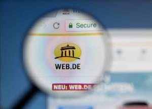 Web.de Logo am PC-Monitor, durch eine Lupe fotografiert