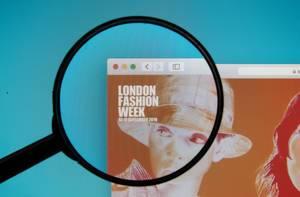 Website der London Fashion Week mit durch Lupe hervorgehobenem Logo auf Computerbildschirm