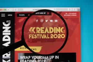 Website des Reading Festivals auf PC-Bildschirm, Lupe hebt das Logo hervor