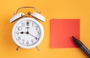 Wecker mit einem leeren roten Zettel und einem Filzstift vor gelbem Hintergrund