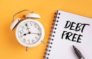 Wecker und ein Heft mit 'Debt-free' Text mit einem Filzstift drauf vor gelbem Hintergrund