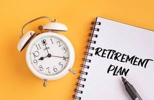 Wecker und ein Heft mit 'Retirement plan' Text mit einem Filzstift drauf vor gelbem Hintergrund