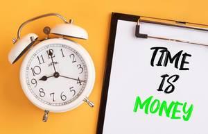 """Wecker und ein Klemmbrett mit dem handgeschriebenen Text """"Time is Money. / Zeit ist Geld"""", vor gelbem Hintergrund"""
