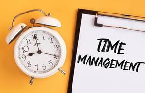 """Wecker und ein Klemmbrett mit dem handgeschriebenen Text """"Time Management / Zeitmanagement"""", vor gelbem Hintergrund"""