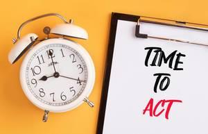 """Wecker und ein Klemmbrett mit dem handgeschriebenen Text """"time to act / Zeit zu Handeln"""", vor gelbem Hintergrund"""
