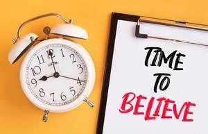 """Wecker und ein Klemmbrett mit dem handgeschriebenen Text """"Time to beliebe / Zeit zu glauben"""", vor gelbem Hintergrund"""