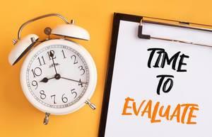 """Wecker und ein Klemmbrett mit dem handgeschriebenen Text """"Time to evaluate / Zeit für die Bewertung"""", vor gelbem Hintergrund"""
