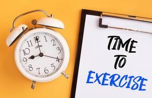"""Wecker und ein Klemmbrett mit dem handgeschriebenen Text """"Time to exercise / Zeit zum Trainieren"""", vor gelbem Hintergrund"""