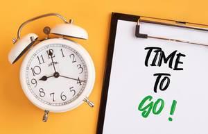 """Wecker und ein Klemmbrett mit dem handgeschriebenen Text """"Time to go! / Zeit zu gehen"""", vor gelbem Hintergrund"""