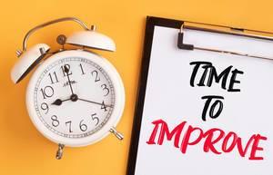 """Wecker und ein Klemmbrett mit dem handgeschriebenen Text """"Time to improve / Zeit sich zu verbessern"""", vor gelbem Hintergrund"""