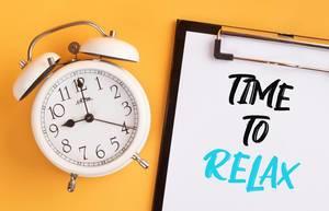 """Wecker und ein Klemmbrett mit dem handgeschriebenen Text """"Time to relax / Zeit um zu entspannen"""", vor gelbem Hintergrund"""