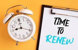 """Wecker und ein Klemmbrett mit dem handgeschriebenen Text """"Time to renew / Zeit zum Erneuern"""", vor gelbem Hintergrund"""
