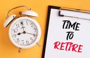 """Wecker und ein Klemmbrett mit dem handgeschriebenen Text """"Time to retire / Zeit in Rente zu gehen"""", vor gelbem Hintergrund"""