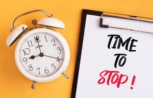 """Wecker und ein Klemmbrett mit dem handgeschriebenen Text """"Time to stop / Es ist Zeit aufzuhören"""", vor gelbem Hintergrund"""
