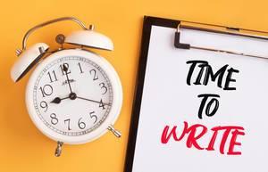 """Wecker und ein Klemmbrett mit dem handgeschriebenen Text """"Time to write / Zeit für das Schreiben"""", vor gelbem Hintergrund"""