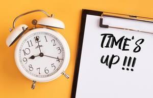 """Wecker und ein Klemmbrett mit dem handgeschriebenen Text """"Time"""