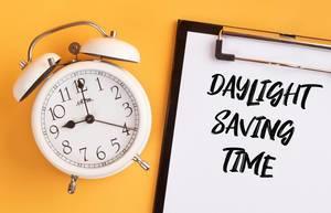 """Wecker und ein Klemmbrett mit dem Text """"Daylight Saving Time / Sommerzeit"""", vor gelbem Hintergrund"""