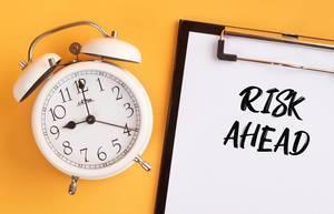 """Wecker und ein Klemmbrett mit dem Text """"Risk ahead / auf einen zukommendes Risiko"""", vor gelbem Hintergrund"""