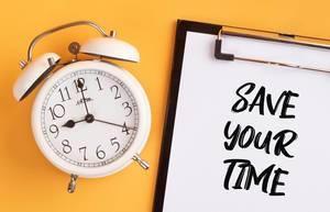 """Wecker und ein Klemmbrett mit dem Text """"Save your time / Zeit sparen"""", vor gelbem Hintergrund"""