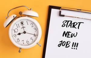 """Wecker und ein Klemmbrett mit dem Text """"start new job / einen neuen Job antreten"""", vor gelbem Hintergrund"""