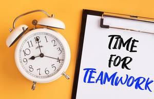 """Wecker und ein Klemmbrett mit dem Text """"Time for Teamwork / Zeit für Teamwork"""", vor gelbem Hintergrund"""