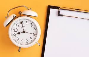 Wecker und ein Klemmbrett mit einem leeren Blatt Papier, vor gelbem Hintergrund