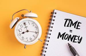 """Wecker und ein Notizblock mit dem Text """"Time is money / Zeit ist Geld"""", mit einem Filzstift vor gelbem Hintergrund"""