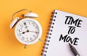 """Wecker und ein Notizblock mit dem Text """"Time to move / Zeit zum Umziehen"""", mit einem Filzstift vor gelbem Hintergrund"""