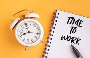 """Wecker und ein Notizblock mit dem Text """"time to work / Zeit zu arbeiten"""", mit einem Filzstift vor gelbem Hintergrund"""