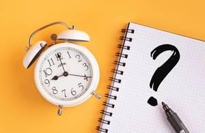 Wecker und ein Notizblock mit einem Fragezeichen und einem schwarzen Filzstift vor gelbem Hintergrund