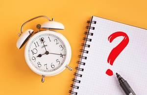 Wecker und ein Notizblock mit einem roten Fragezeichen und einem Filzstift vor gelbem Hintergrund