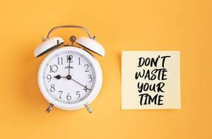 Wecker und ein Zettel mit 'Don't waste your time!' Text vor gelbem Hintergrund