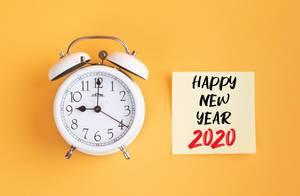 Wecker und ein Zettel mit 'Happy new year 2020' Text vor gelbem Hintergrund