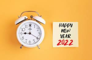 Wecker und ein Zettel mit 'Happy new year 2022' Text vor gelbem Hintergrund