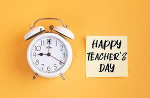 Wecker und ein Zettel mit 'Happy teacher's day' Text vor gelbem Hintergrund