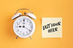 Wecker und ein Zettel mit 'Last hour offer' Text vor gelbem Hintergrund