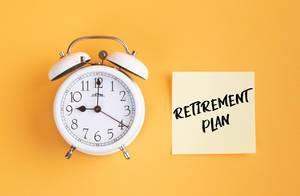 Wecker und ein Zettel mit 'Retirement plan' Text vor gelbem Hintergrund