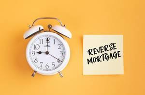 Wecker und ein Zettel mit 'Reverse mortgage' Text vor gelbem Hintergrund