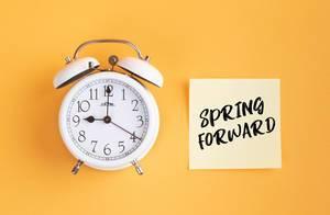 Wecker und ein Zettel mit 'Spring forward' Text vor gelbem Hintergrund